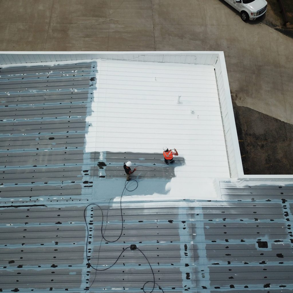 Overhead view of workers adding coating onto a roof.