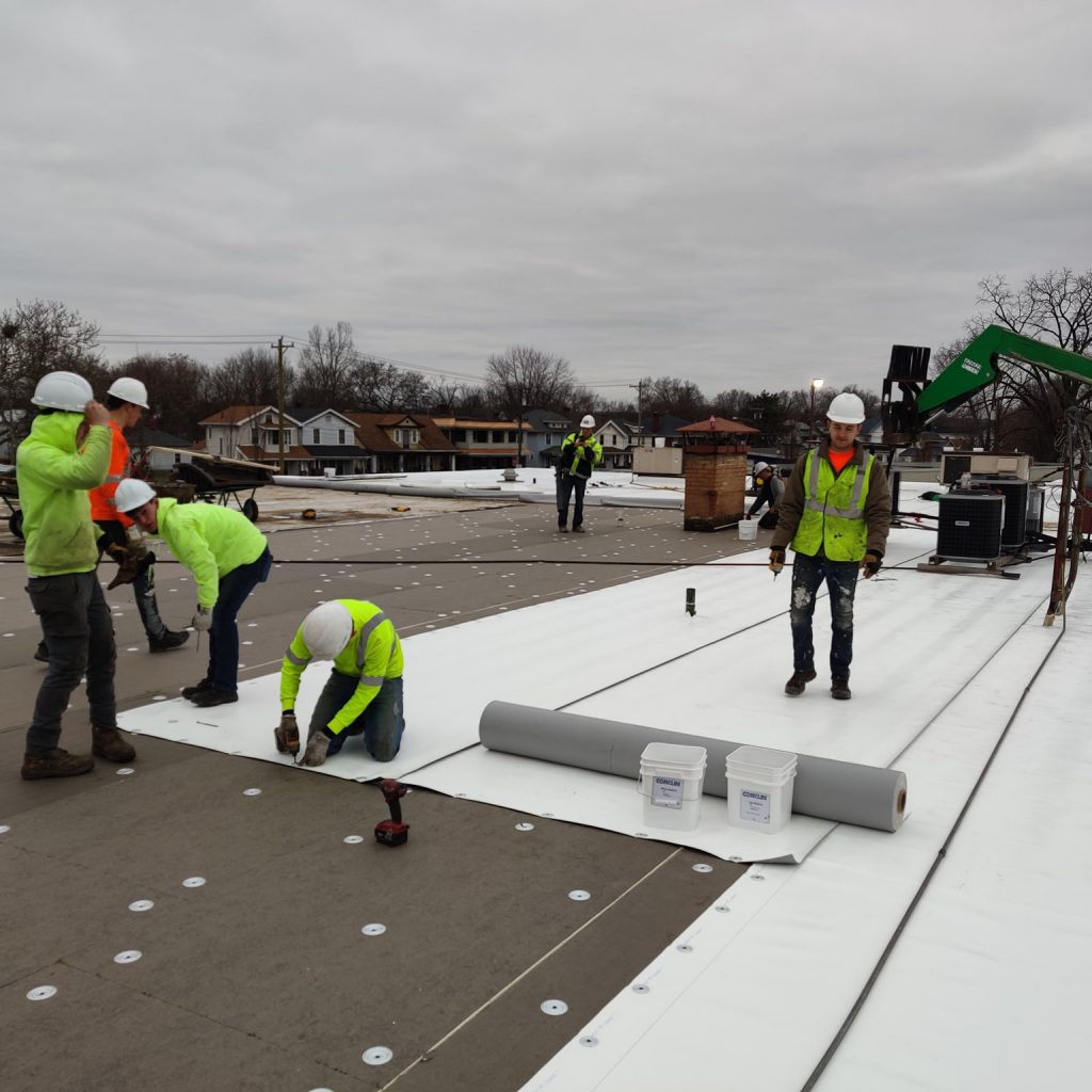 TPO membrane being placed on top of a roof by a team of workers.